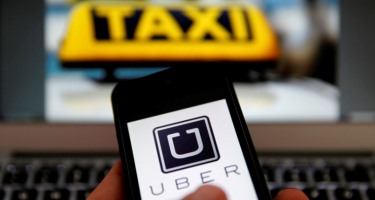 An illustration picture shows the logo of car-sharing service app Uber on a smartphone next to the picture of an official German taxi sign in Frankfurt, September 15, 2014. A Frankfurt high court will hold a hearing on a recent lawsuit brought against Uberpop by Taxi Deutschland on Tuesday.  San Francisco-based Uber, which allows users to summon taxi-like services on their smartphones, offers two main services, Uber, its classic low-cost, limousine pick-up service, and Uberpop, a newer ride-sharing service, which connects private drivers to passengers - an established practice in Germany that nonetheless operates in a legal grey area of rules governing commercial transportation. The company has faced regulatory scrutiny and court injunctions from its early days, even as it has expanded rapidly into roughly 150 cities around the world.   REUTERS/Kai Pfaffenbach (GERMANY - Tags: BUSINESS EMPLOYMENT CRIME LAW TRANSPORT)